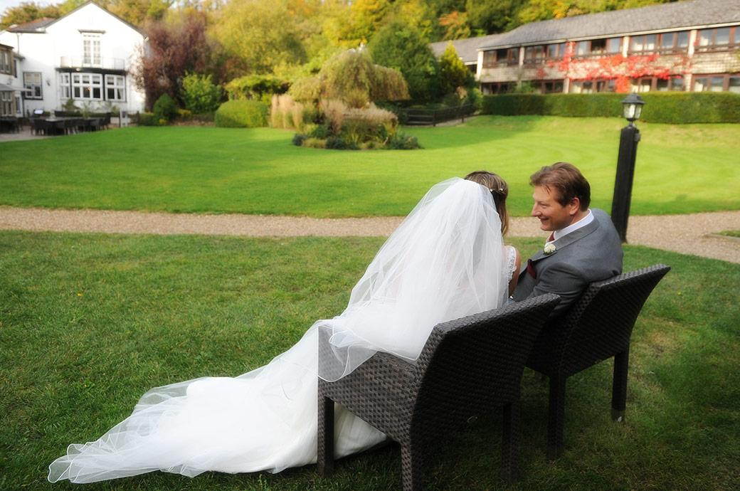 Groom and Bride take some time out from the Burford Bridge Hotel wedding reception in Dorking Surrey to sit down for a chat on a garden chair
