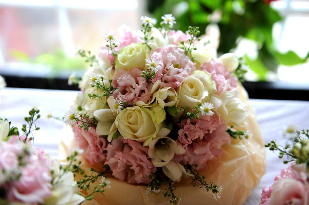 Fresh looking Bridal bouquet bursting with pink yellow and white flowers ready for the Bride before her marriage and reception at Surrey wedding venue Burford Bridge Hotel