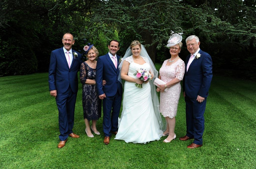 Family wedding photo of the newlyweds with their mothers and fathers captured in the lovely lawn area at the back of Burford Bridge Hotel Surrey at the bottom of Box Hill