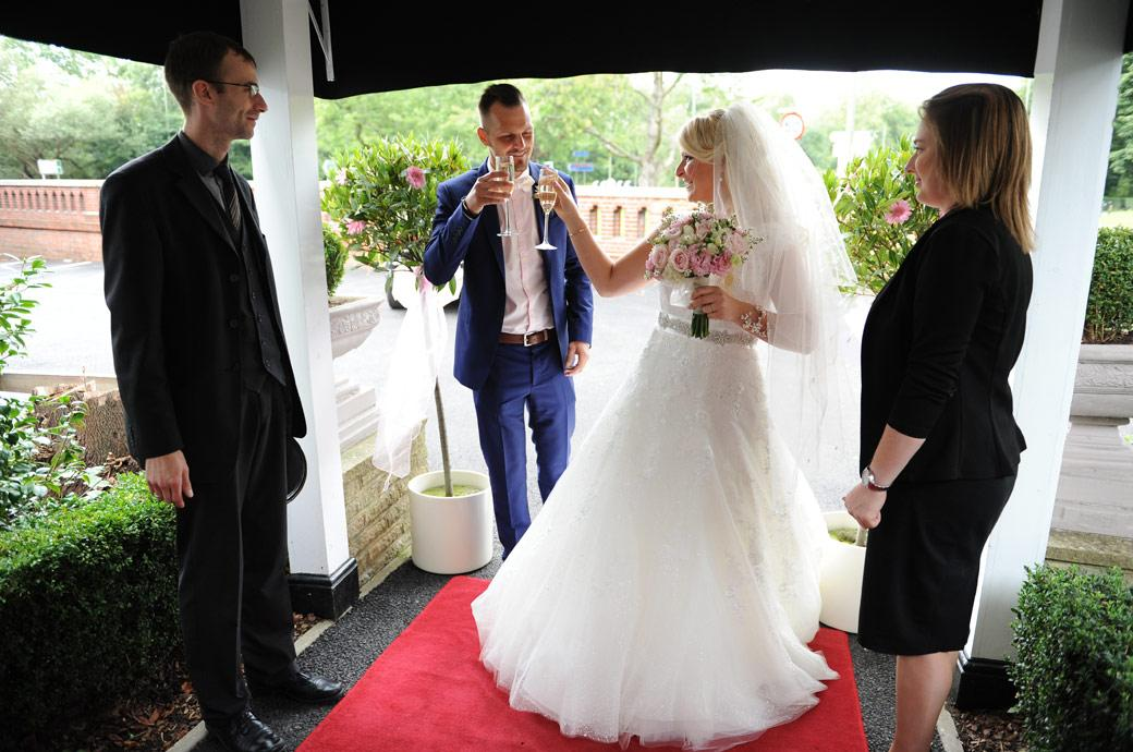 Bride and Groom celebrate with champagne on arriving at Surrey wedding venue Burford Bridge Hotel pictured standing on the red carpet in the Tithe Barn entrance