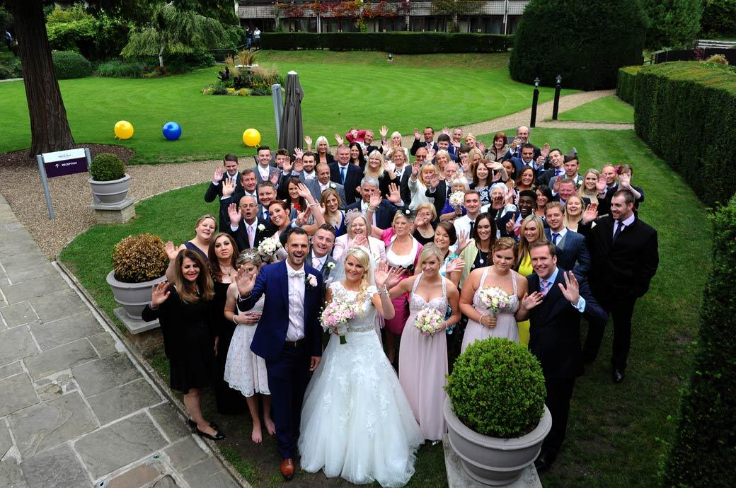 All fun smiles and waves for the everyone at the wedding photo taken at Burford Bridge Hotel Surrey from the metal staircase outside the Tithe Barn
