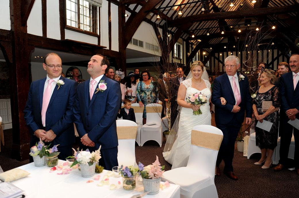 An emotional Groom welling up in this wedding photo taken at Surrey wedding venue the Burford Bridge Hotel as he awaits his bride to reach him down the Tithe Barn aisle