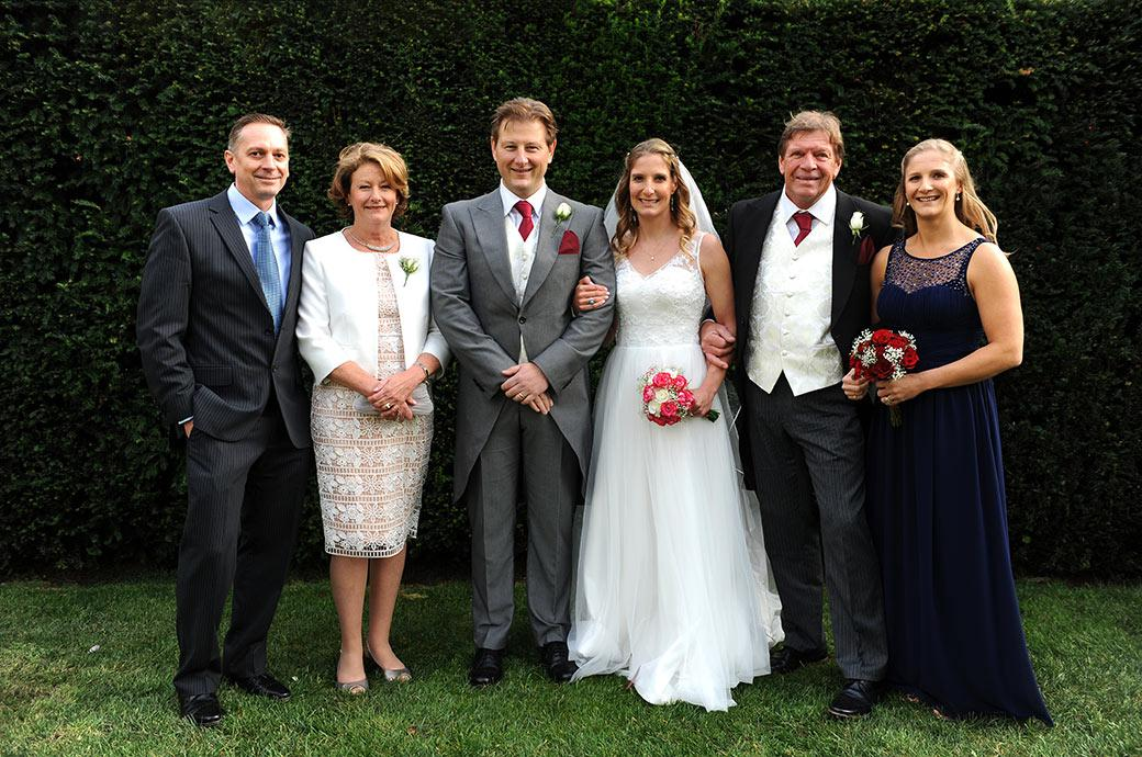 Relaxed group family wedding photograph taken at Surrey wedding venue Burford Bridge Hotel outside the Tithe Barn on the lawn