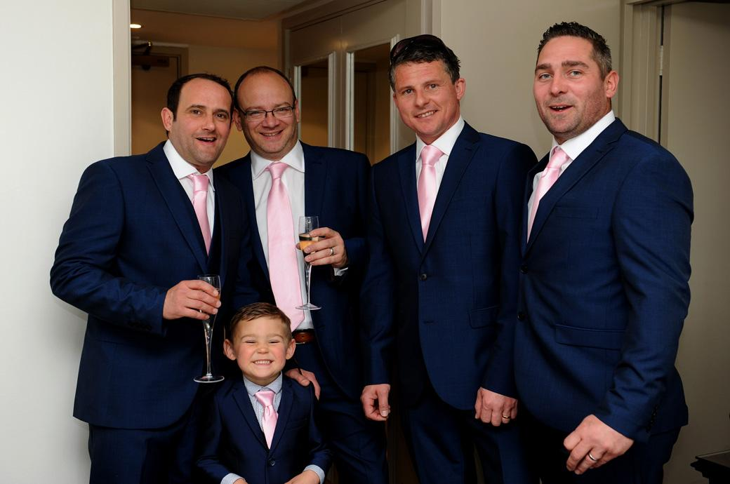Groom with champagne in hand looking smart with the boys in this wedding picture captured at Burford Bridge Hotel by a Surrey Lane wedding photographer