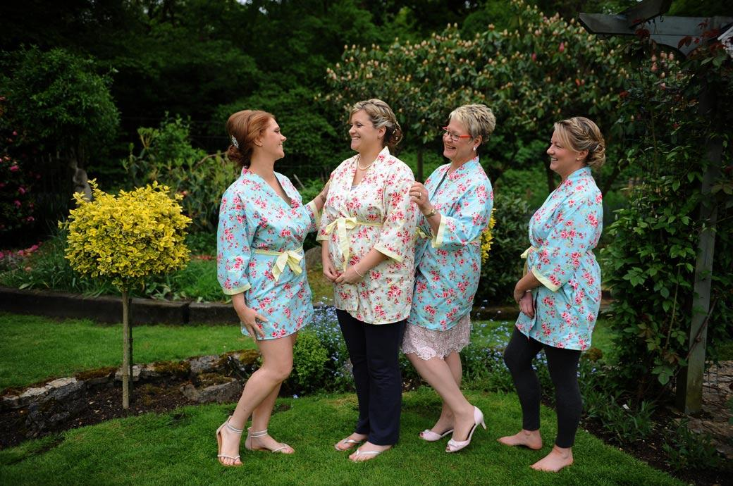 Bride Mum and Bridesmaids in floral dressing gowns having fun before dressing for the marriage ceremony at Surrey wedding venue Burford Bridge Hotel