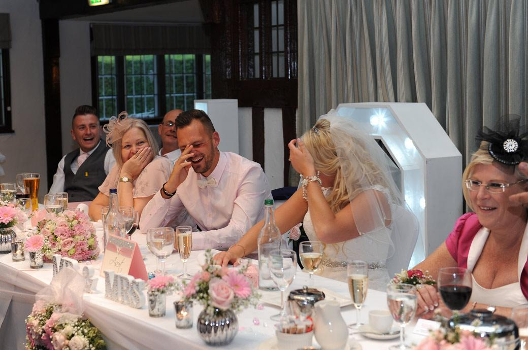 Bride and Groom sitting at the top table in stitches of laughter during the funny wedding speeches held in in The Tithe Barn at Burford Bridge Hotel in Surrey