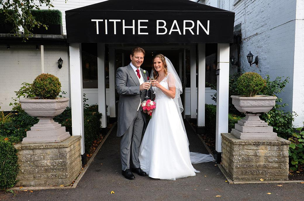 Happy smiling Bride and Groom clink their glasses of champagne together at Surrey wedding venue Burford Bridge Hotel outside the entrance to the Tithe Barn