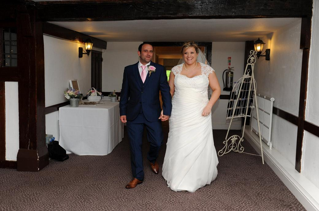 Wedding photo of the Bride and Groom entering the Tithe Barn for their wedding breakfast captured at the Burford Bridge Hotel by Surrey Lane wedding photographers