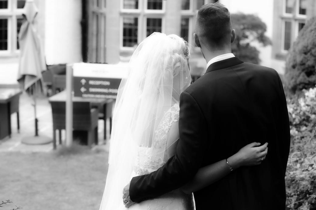 A moody romantic wedding photo from behind of the Bride and Groom standing with arms around each other at Burford Bridge Hotel wedding venue in Dorking Surrey