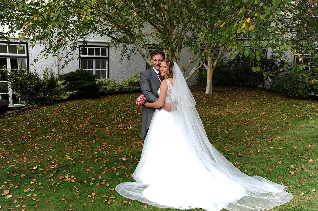 Happiness and smiles for the Bride and groom as they embrace on the lawn at Surrey wedding venue Burford Bridge Hotel situated at the bottom of Box Hill