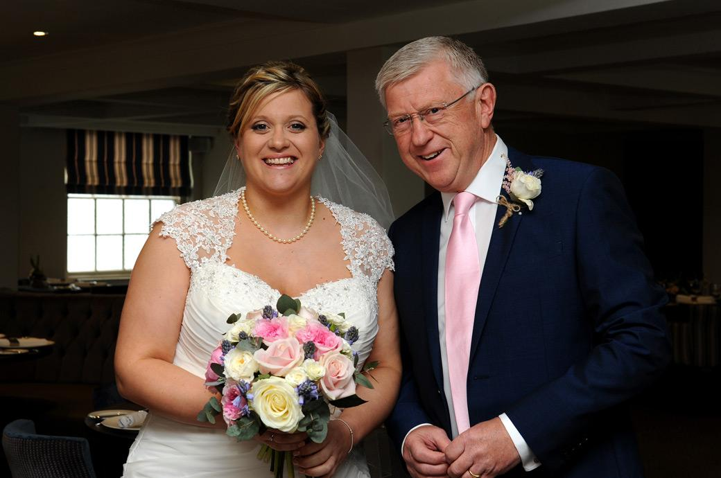 Happy smiling Bride and father captured in this wedding photograph ready at Surrey wedding venue the Burford Bridge Hotel to walk into the Tithe Barn ceremony room