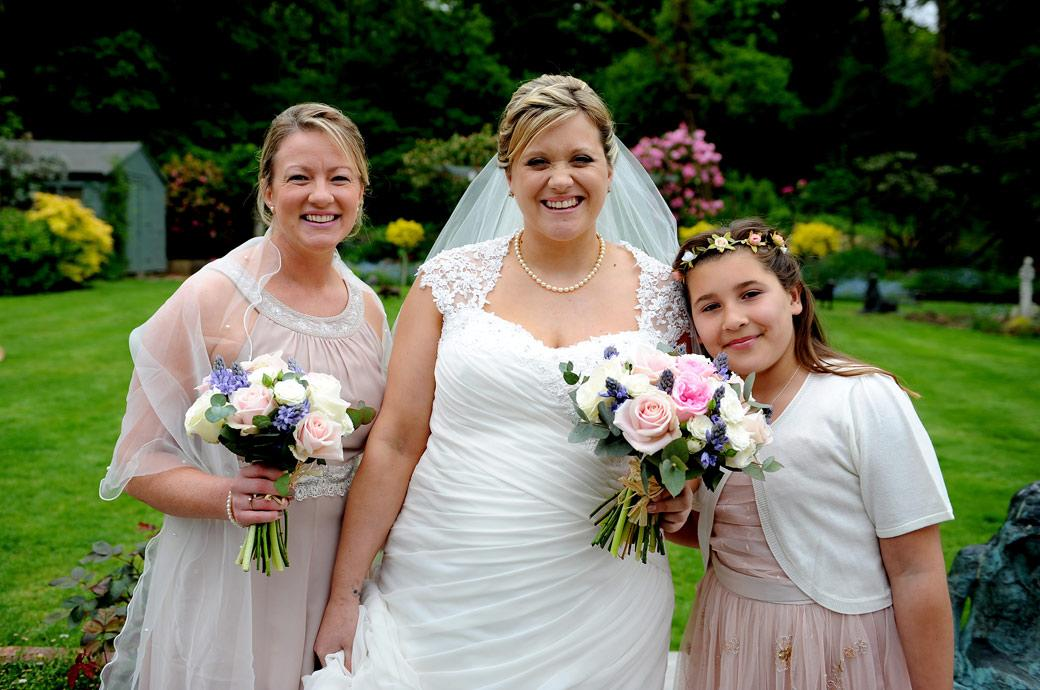 Smiling Bride with a Bridesmaid and flower girl all dressed and ready in the parent's garden and ready to leave for the nearby Surrey wedding venue Burford Bridge Hotel