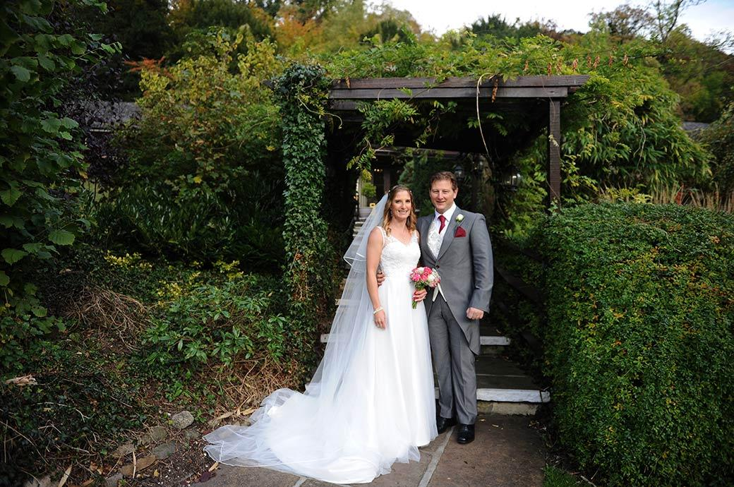 Content and happy Bride and groom standing by the arbour in the relaxing garden area at the popular Burford Bridge Hotel Surrey wedding venue in Dorking