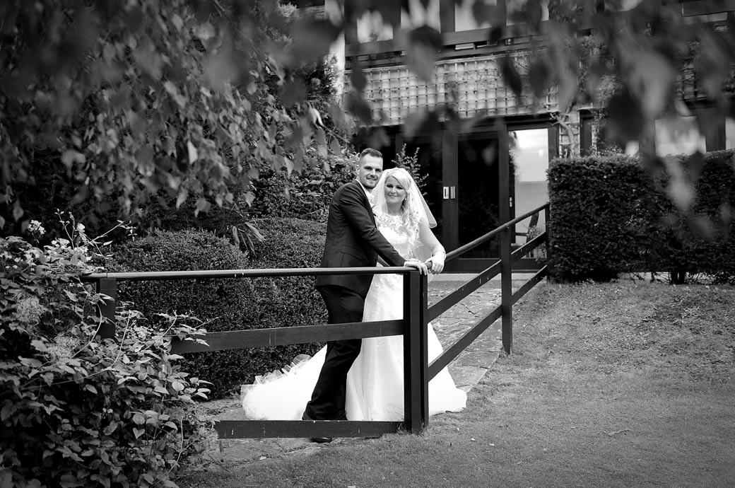 Wedding picture of the Bride and Groom standing by a wooden garden railing at Surrey wedding venue Burford Bridge Hotel taken from under a tree