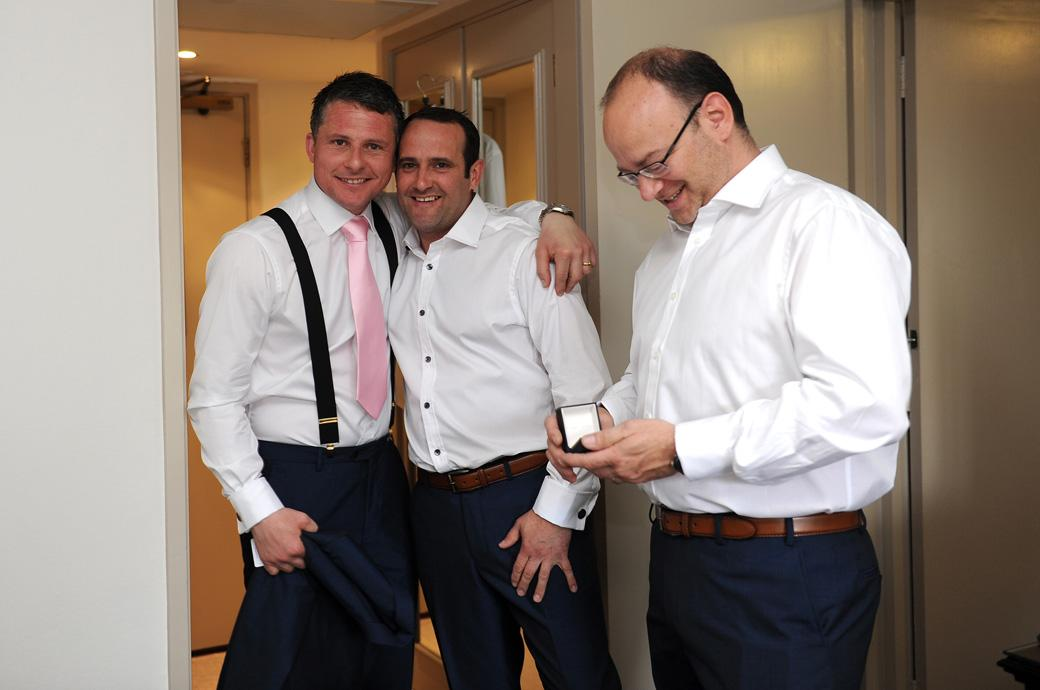 Nervous but smiling Groom captured in this wedding photo with the boys taken as he gets ready for his marriage at Burford Bridge Hotel in Surrey in the ancient Tithe Barn