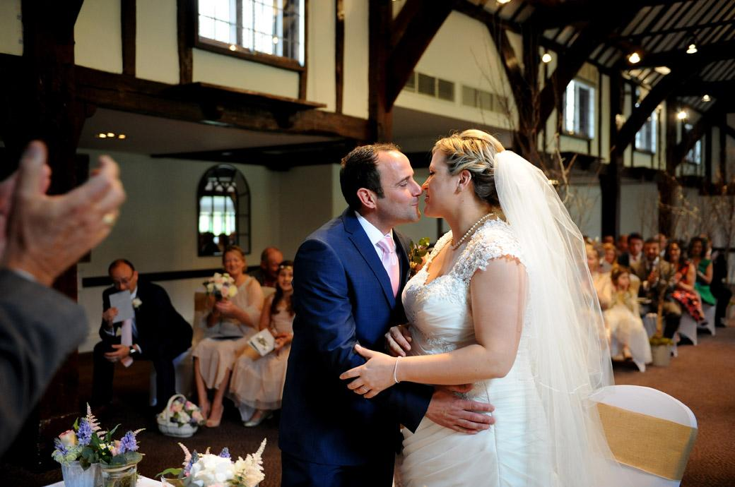 Wedding photo of a just married couple embracing each other and going in for a kiss in the Tithe Barn at Surrey venue Burford Bridge Hotel at the bottom of Box Hill