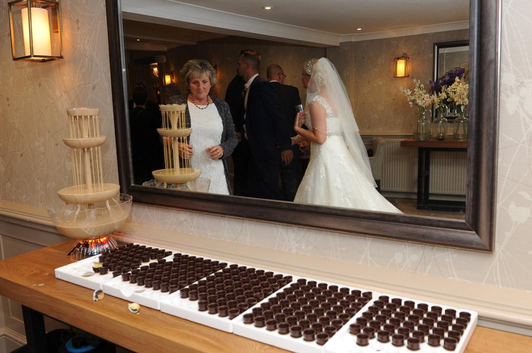 A lady eyes up the Tia Maria fountain complete with chocolate cups captured by a Surrey Lane wedding photographer at the Burford Bridge Hotel in Dorking