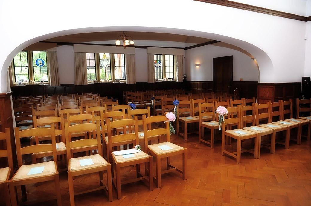 A wedding photograph of the Burrows Lea Country House simple wooden finished and low ceilinged chapel dressed and awaiting the guests at this lovely wedding venue in  Shere Surrey