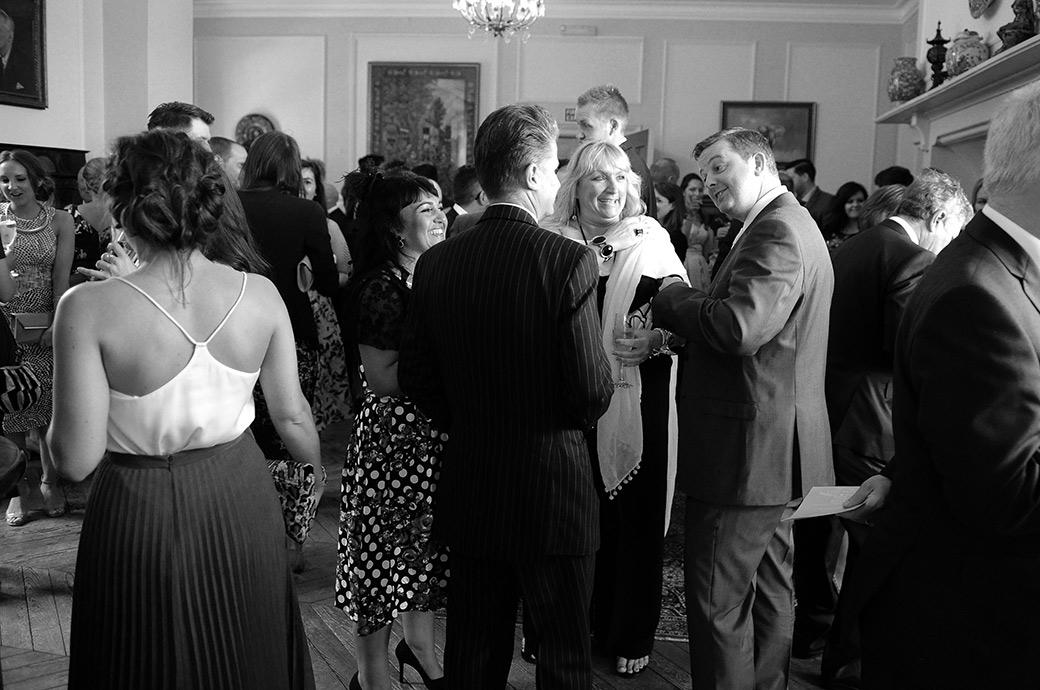 Wedding guests enjoying a chat over champagne after the marriage ceremony in Surrey at the wonderful Burrows Lea Country House a tranquil and rural wedding venue