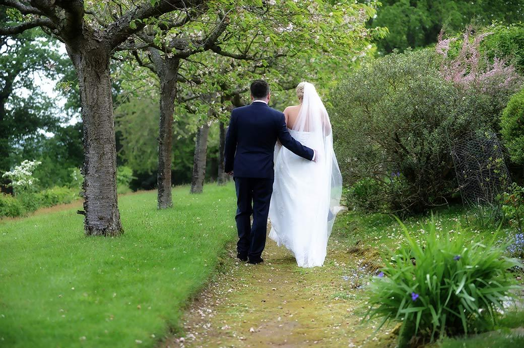 Back shot wedding photograph of a Bride and groom walking away down the lovely Cherry Tree Walk in the beautiful Surrey countryside a round Burrows Lea Country House