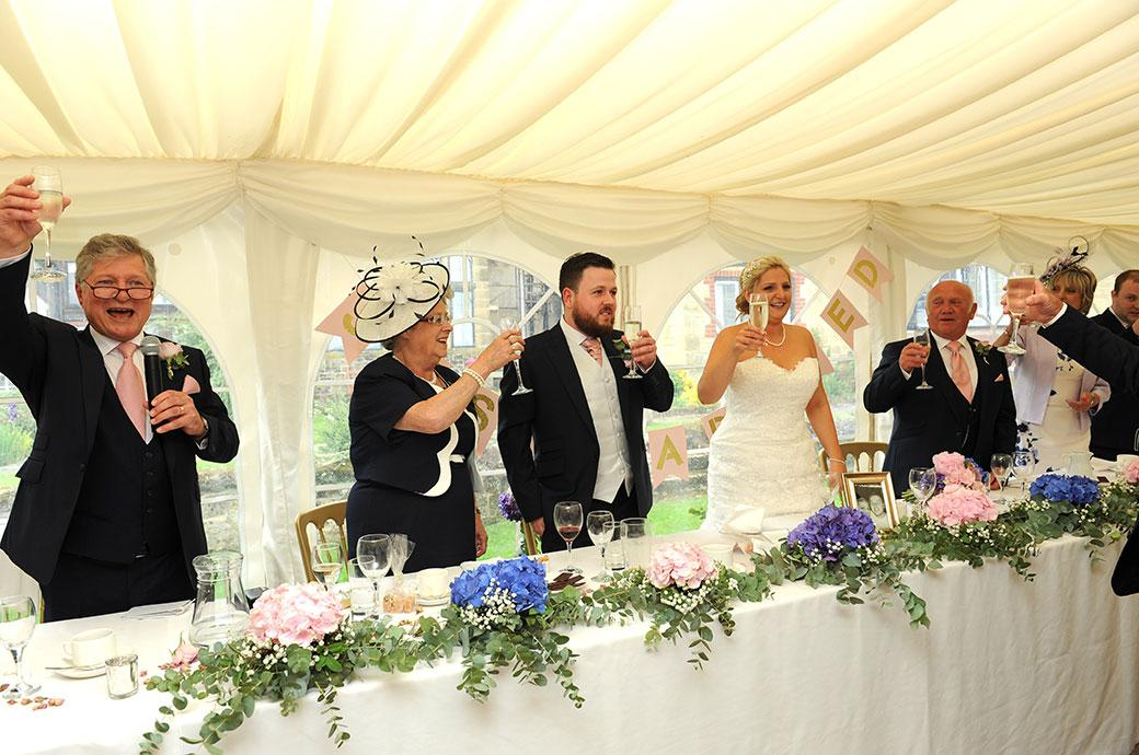Wedding picture of the head table at Burrows Lea Country House in Shere Surrey raising their champagne glasses for the final toast to the happy newlywed couple