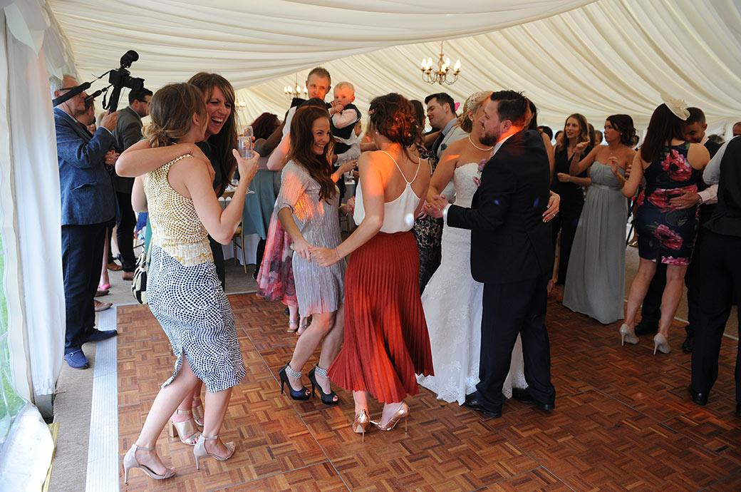 Fun and laughter for the bride and groom and their guests at Burrows Lea Country House in Shere Surrey as everyone lets loose on the dance floor