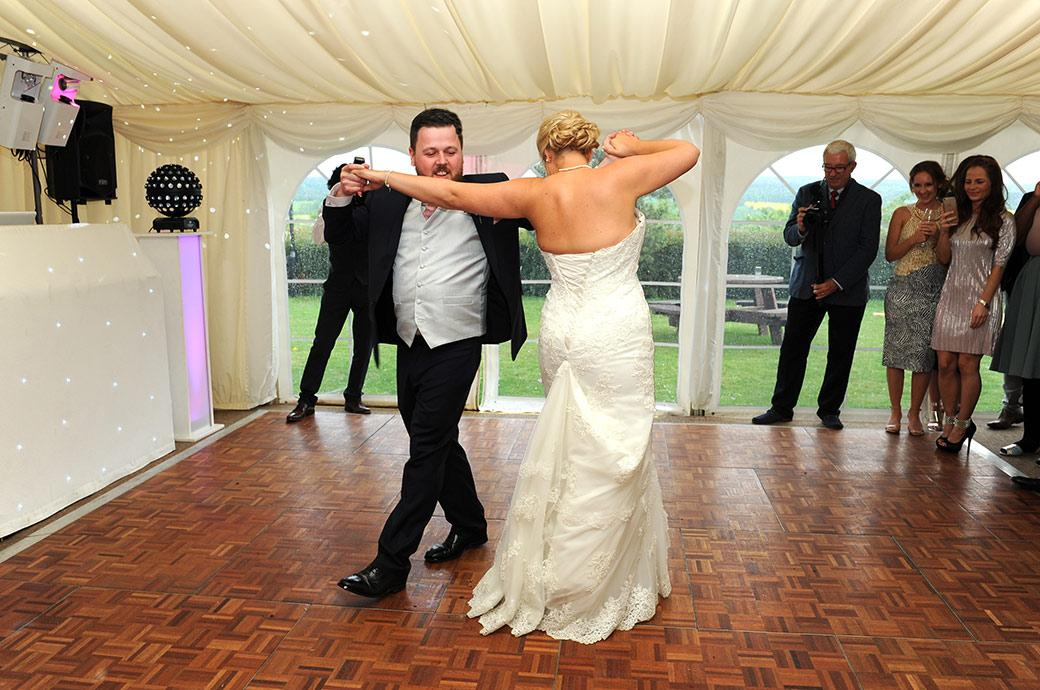 Newlywed couple swing in unison as they deftly complete a move during their first dance at Surrey wedding venue Burrows Lea Country House in Shere