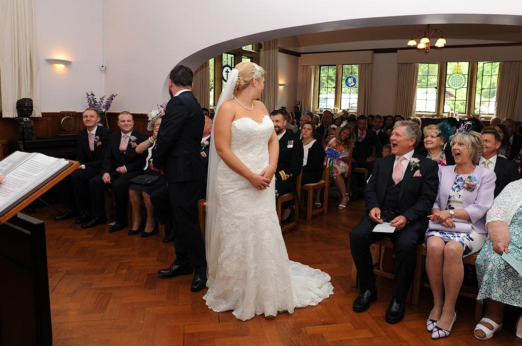 Bride and Groom at the start of their marriage ceremony in the Surrey wedding chapel at Burrows Lea Country House turn around for any objections amidst the laughter of their family