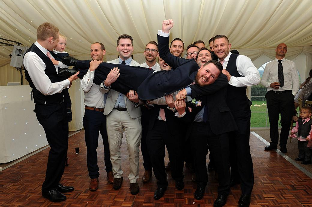 Joyful smiling Groom having fun as he is lifted up into the air by his stags at  Burrows Lea Country House in Shere Surrey during the post wedding breakfast entertainments