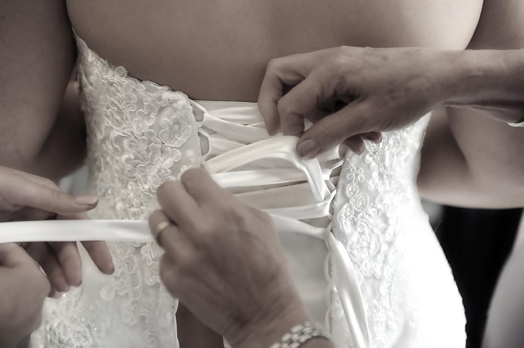 A classic lacing up the Bride's wedding dress picture captured here at the lovely Burrows Lea Country House by a Surrey Lane wedding photographer