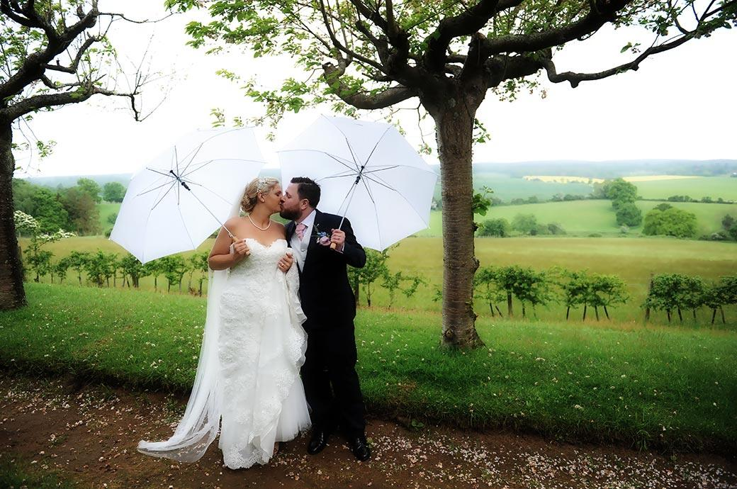 Newlyweds captured by Surrey Lane wedding photographers at Burrows Lea Country House as they kiss along the lovely Cherry Tree Walk with white umbrellas in hand