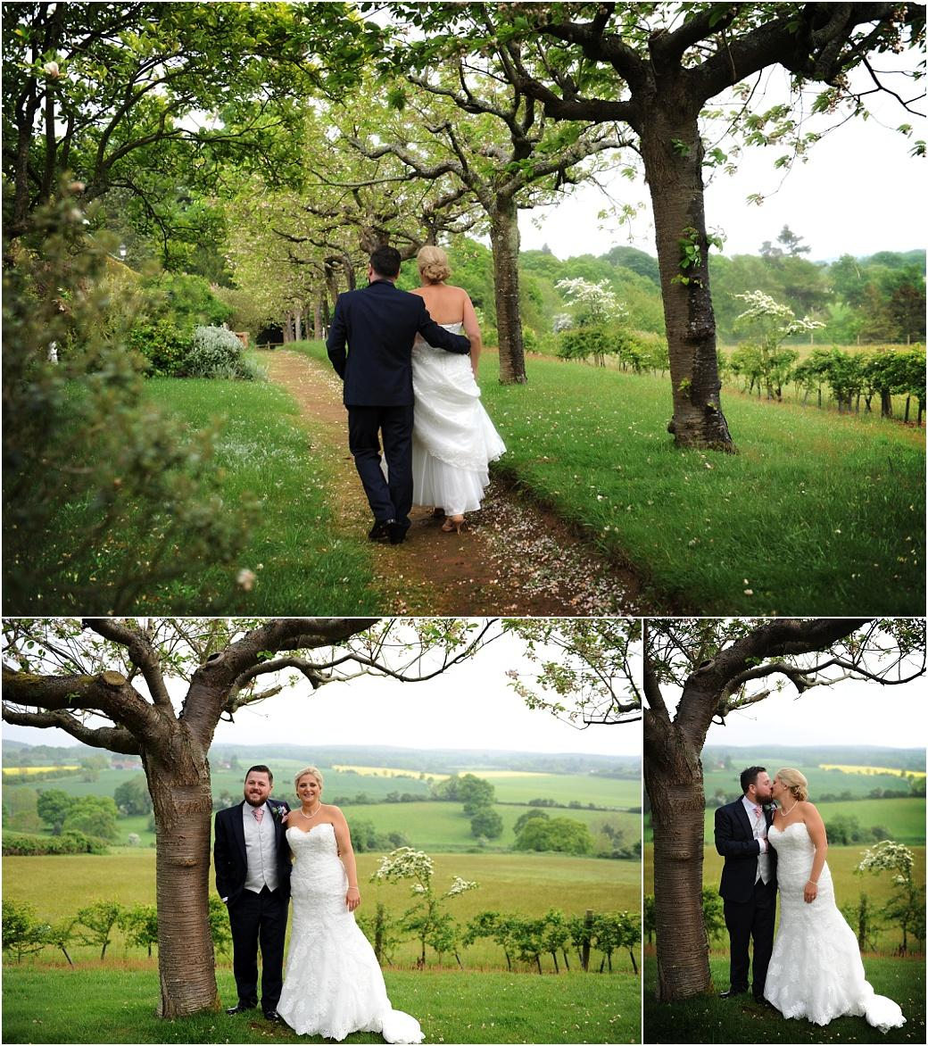 Bride and groom enjoying a romantic and scenic walk along the beautiful Cherry Tree Walk at Burrows Lea Country House with its stunning views over the Surrey Hills