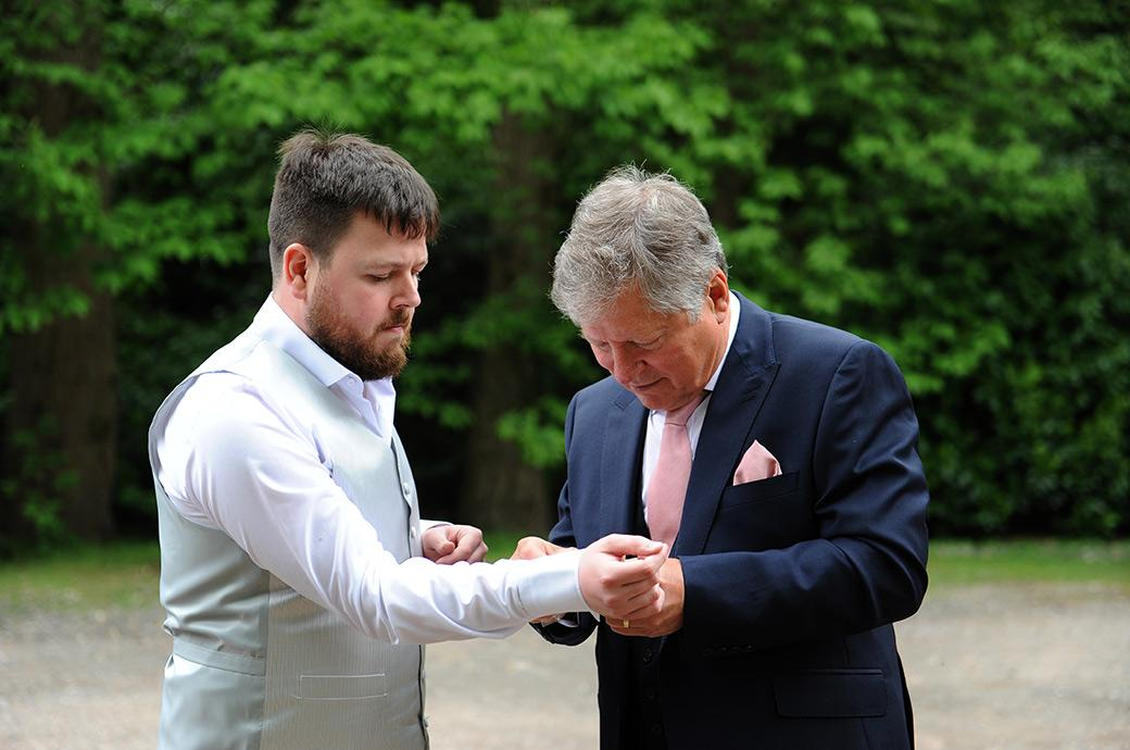 A slightly nervous groom is given a hand from his father in law with his cufflinks as he gets ready for his Burrows Lea Country House wedding in the Surrey countryside