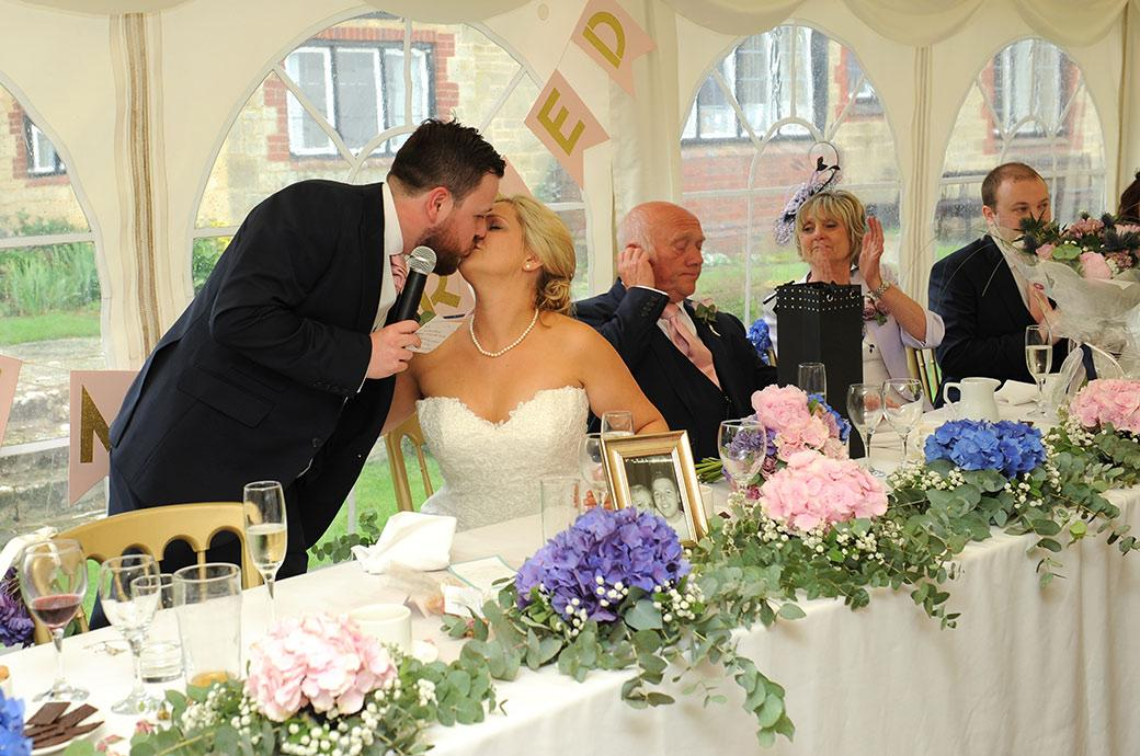 Groom kisses his wife at the end of his wedding speech captured in this sweet picture taken at the wonderfully inviting Surrey wedding venue Burrows Lea Country House