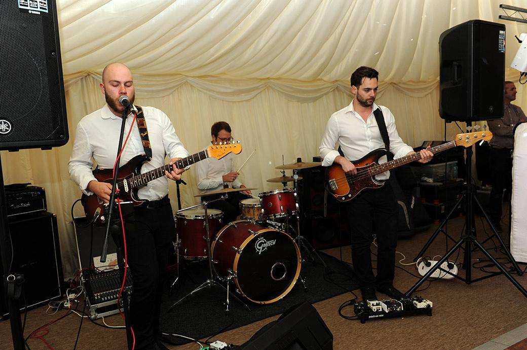 Wedding band in action as they herald the start of the dancing and evening celebrations at the Burrows Lea Country House wedding venue in Surrey near green and leafy Shere village