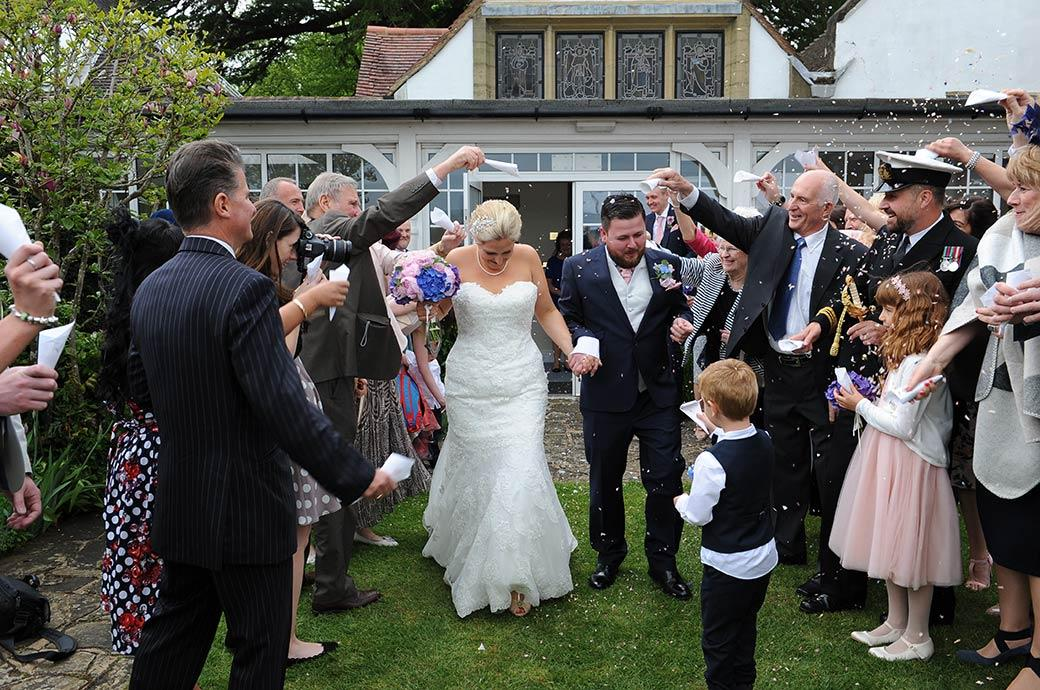 Wedding picture of the Bride and groom heads down as they dodge the shower of confetti on the lawn outside the chapel at Burrows Lea Country House wedding venue in Surrey
