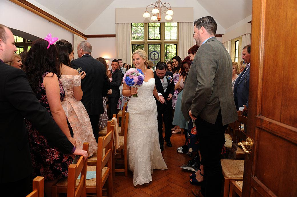 A smiling and joyous Bride at Burrows Lea Country House in Shere Surrey leads her groom down the narrow side aisle of the chapel as husband and wife