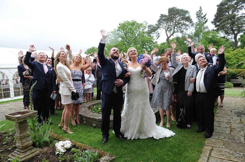Happy newlyweds and their guests waving with gusto up at the Surrey Lane wedding photographer on the Burrows Lea Country House fire escape stairs for the everyone photo