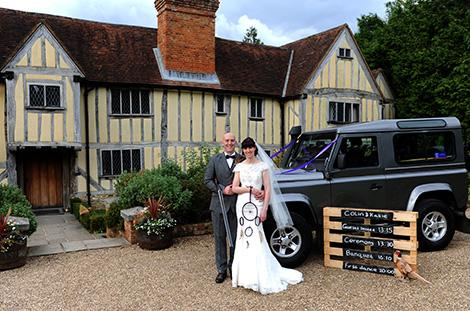 Smiling Groom and Bride standing with a shotgun and dream catcher outside the rustic Surrey wedding venue Cain Manor in Churt alongside their silver Landrover wedding car