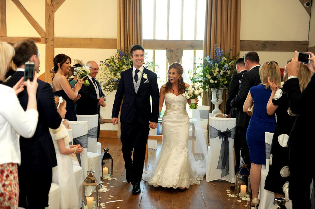 The proud Groom takes his beaming wife down the aisle in the music Room after getting married at Cain Manor in Surrey captured in this happy wedding photography