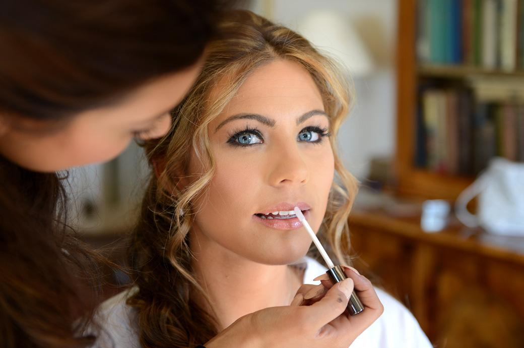 A beautiful excited Bride having lip gloss applied in this wedding picture taken as she gets ready before leaving for her marriage at Surrey wedding venue Cain Manor in Churt