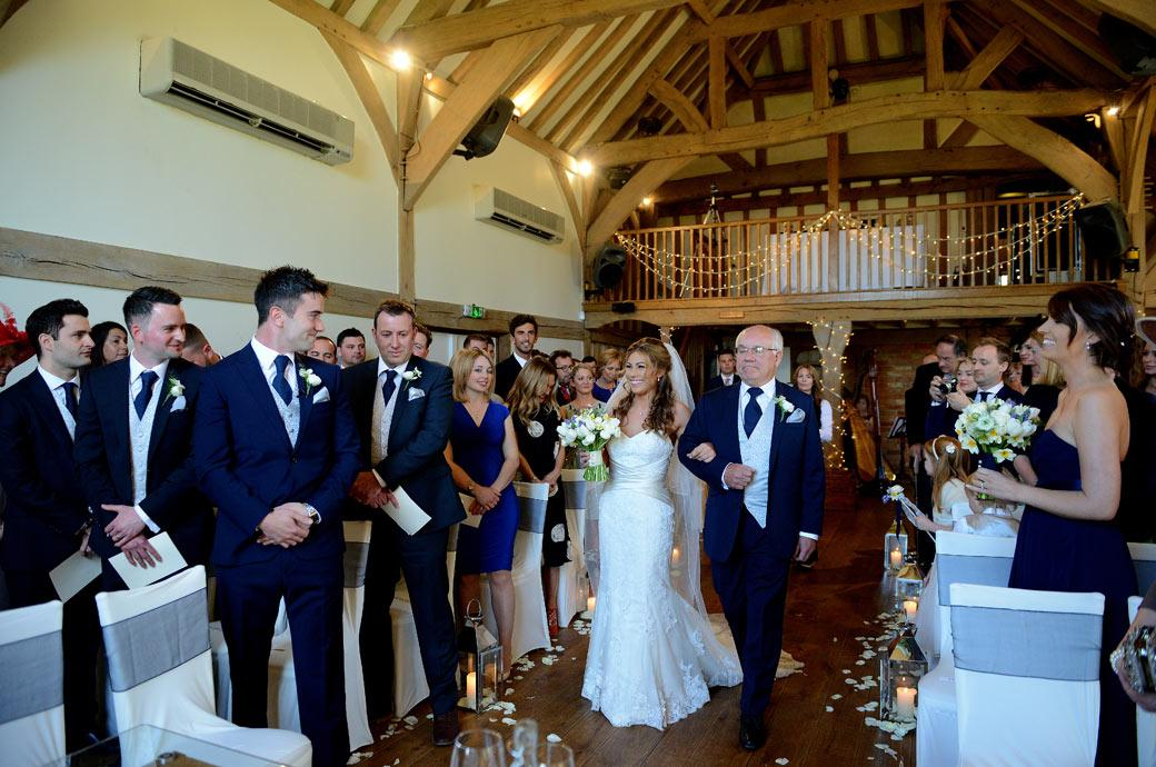 Proud father escorts his happy smiling daughter down the aisle in this delightful wedding picture captured at Surrey wedding venue Cain Manor in the Music Room