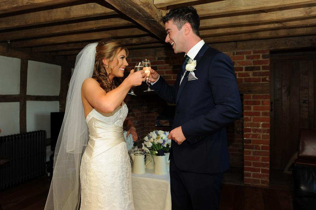 Wedding photo of a happy joyful Bride and Groom celebrating their marriage outside the Music Room at Surry wedding venue Cain Manor with champagne and smiles
