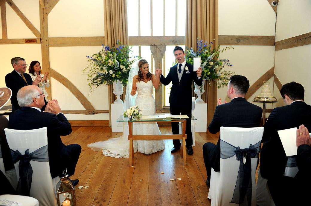 Happy Cain Manor newlyweds raise their marriage certificate and their hands in the air as they celebrate the event in the Music Room at this wonderful wedding venue in Surrey