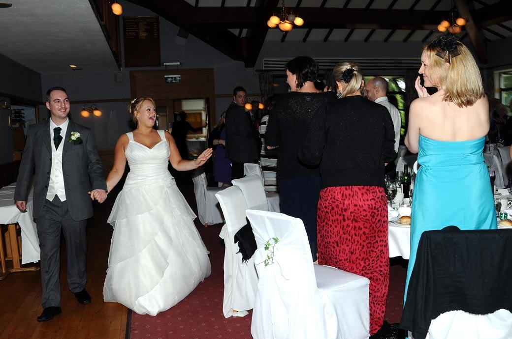 A wonderfully happy wedding picture of an ecstatic Bride as she walks into the wedding breakfast with her husband at Camberley Heath Golf Club Surrey