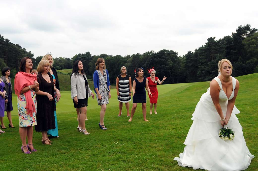 A colourful and fun wedding picture of the bride preparing to throw her bouquet to the expectant ladies captured at Camberley Heath Golf Club Surrey