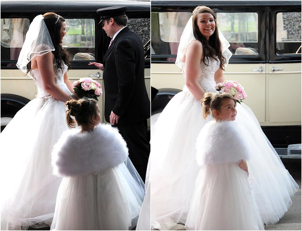 Lovely smiling Bride with flower girl in dazzling white arriving for her wedding and reception in Beddington at Surrey wedding venues St Mary's Church and Carew Manor next door