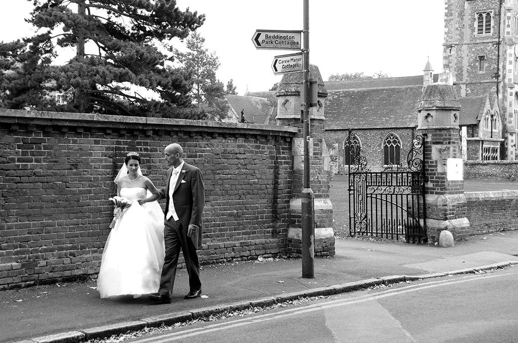 Wedding photo of the Bride and groom walking down the path from two linked Surrey wedding venues Carew Manor and St Mary's Church Beddington adjacent