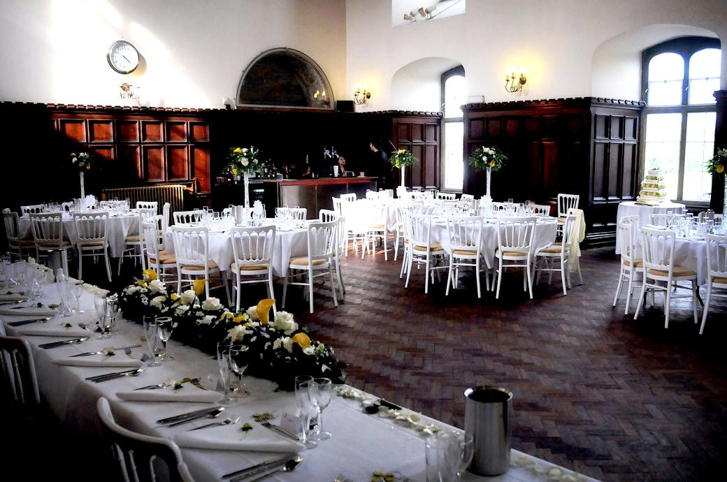 The rich evocative wedding breakfast setting at Surrey wedding venue Carew Manor in the 16th Century Tudor Great Hall before the arrival of the guests