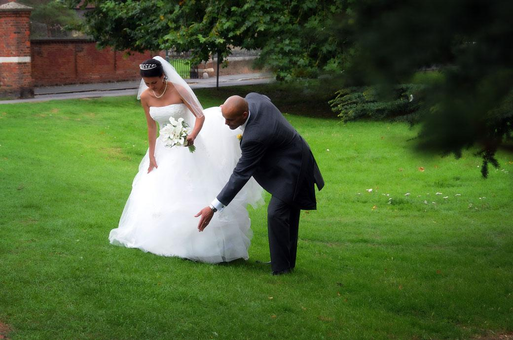 Groom carefully adjusts his Bride's beautiful dress on the grass over the road from Surrey wedding venue Carew Manor an ancient Beddington estate